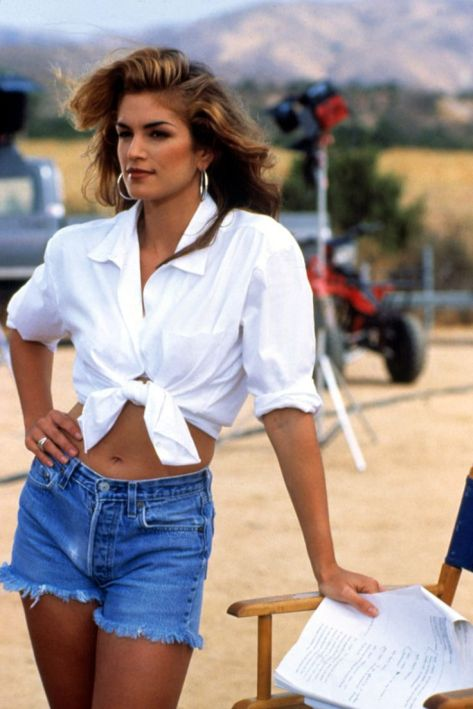 Cindy Crawford con camisa blanca estilo masculino anudada a la cintura